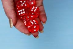 Dados vermelhos em uma pilha em uma mão em um fundo azul Fotos de Stock Royalty Free