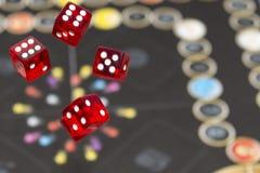 Dados vermelhos no fundo escuro, no conceito do risco, no jogo e na possibilidade Imagens de Stock