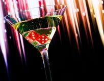 Dados vermelhos no vidro de cocktail no inclinação colorido com espaço para o texto Foto de Stock