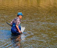 Man wearing blue waders in Kumgang river. Daejeon, South Korea-November, 14,2017: Man wearing blue waders and a basket tied to his waist fishing in Kumgang river Royalty Free Stock Images