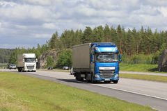 DAF Trucks Transport Merchandise in Traffic. Blue and white DAF XF semi trailer trucks transport goods along motorway among traffic on a beautiful day of summer Royalty Free Stock Photography