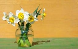 Daffodils σε ένα βάζο γυαλιού στο ξύλινο υπόβαθρο Στοκ εικόνα με δικαίωμα ελεύθερης χρήσης