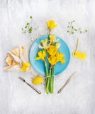 Daffodils bunch on a blue plate with Easter egg , table holiday decoration Royalty Free Stock Image