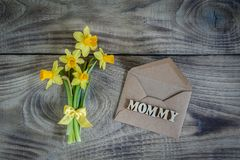 Daffodils with envelope on wooden background. Greeting card. royalty free stock photo