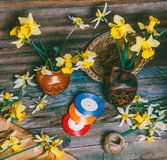 Daffodils flowers in ceramic jugs and scattered on a table. Kraft paper and multi-colored ribbons on a wooden table in a retro rustic style Stock Photo