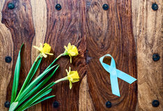 Daffodils and Prostate Cancer Ribbon on Rustic Table Stock Image
