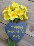 Daffodils with slate heart. Bunch of daffodils with slate heart and 'happy mother's day' text on a wooden background Royalty Free Stock Photography