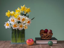 Daffodils in a vase of glass and easter eggs Stock Photography