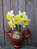Daffodils in a vase on a wooden background. Daffodils in a vase in the shape of a rooster on wooden background gray boards Royalty Free Stock Photography