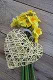 Daffodils with wicker heart. Bunch of daffodils with wicker heart on a wooden background Royalty Free Stock Images