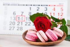 Dag för begreppsvalentin` s, röd ros och bakelser på bakgrund på Arkivfoton