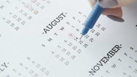 7. dag för kvinnahandcirkel av det august på pappers- kalender lager videofilmer