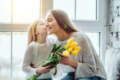 Dag för mödrar för Ð- appy! Barnet gratulerar modern och ger en bukett av blommor till tulpan royaltyfria foton