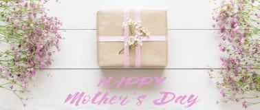 Dag för moder` s, vit trätabell med rosa färgblommor och en gåva royaltyfria bilder
