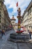 Dag för punkt för sikt för låg vinkel för staty för springbrunn för Bern City Switzerland gatavatten solig mulen arkivbild