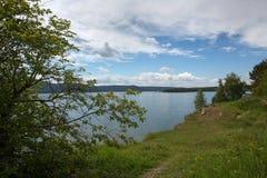 Dag för sommar för flodbank solig, vita moln royaltyfri foto