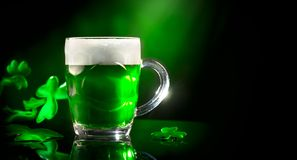 Dag för St Patrick ` s Grön halv liter för öl över mörker - grön bakgrund som dekoreras med treklöversidor royaltyfri fotografi