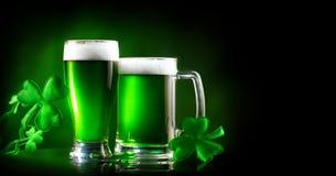 Dag för St Patrick ` s Grön halv liter för öl över mörker - grön bakgrund som dekoreras med treklöversidor arkivfoton