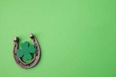 Dag för St Patricks, lyckliga berlock Horesechoe och treklöver på grön bakgrund Arkivbilder