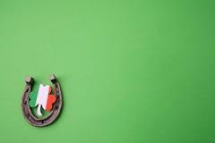 Dag för St Patricks, lyckliga berlock Horesechoe och treklöver på grön bakgrund Royaltyfria Bilder