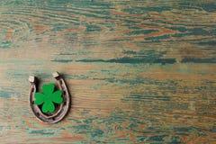 Dag för St Patricks, lyckliga berlock Horesechoe och treklöver på träbakgrund Royaltyfria Foton