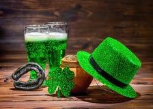 Dag för St Patricks med exponeringsglas av grönt öl, bladväxt av släktet Trifolium, leprech Arkivbilder