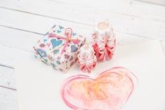 Dag för St-valentin` s: två sned stearinljus av rosa färger färgar, den packade gåvan och den stora hjärtan Royaltyfri Bild
