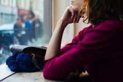 Dag för ung kvinna som drömmer vid fönstret Arkivfoton