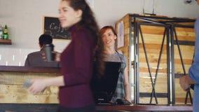 Dag för upptaget arbete på det hemtrevliga kafét med linjen av kunder som står på räknaren som betalar med smartphonen och köpand arkivfilmer