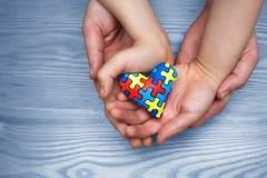 Dag för världsautismmedvetenhet, pussel eller figursågmodell på hjärta med autistiska barns och faderhänder royaltyfri fotografi