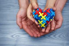 Dag för världsautismmedvetenhet, pussel eller figursågmodell på hjärta med autistiska barns och faderhänder royaltyfri foto
