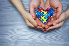 Dag för världsautismmedvetenhet, pussel eller figursågmodell på hjärta med autistiska barns och faderhänder arkivfoto