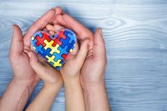 Dag för världsautismmedvetenhet, pussel eller figursågmodell på hjärta med autistiska barns och faderhänder arkivbilder