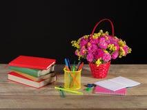 Dag för världslärare` s Stilleben med det bokhögen, blommor, papper och skrivbordet på svart bakgrund royaltyfria bilder