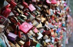 Dag för valentin` s - många hänglås på en bro - röd hänglås med H royaltyfri bild
