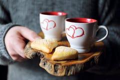 Dag för valentin` s: två koppar kaffe i händerna och hjärtan för man` s Fotografering för Bildbyråer