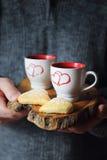 Dag för valentin` s: två koppar kaffe i händerna och hjärtan för man` s Royaltyfria Bilder
