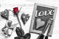 Dag för vykortvalentin` s Hemlagade hjärtor, rosor, dekorativ ram, gåvaask med pilbågen och champagne på en ljus träbakgrund, Royaltyfri Foto