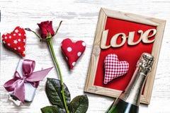 Dag för vykortvalentin` s Hemlagade hjärtor, rosor, dekorativ ram, gåvaask med pilbågen och champagne på en ljus träbakgrund, Arkivfoton