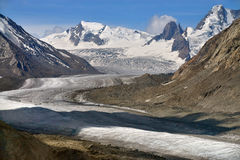Dag Tug glacier: a huge firn glove tongue, gray moraine at the edges and high, snow-capped mountain peaks in the background, a sum Stock Photo