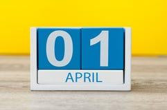 1 Dag 1 van april van april-maand, kalender op gele achtergrond De lentetijd, Pasen en dwazendag Stock Foto's