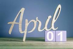 1 Dag 1 van april van maand, dagelijkse kalender op houten lijst met purpere of violette achtergrond Het thema van de de lentetij Stock Foto's