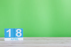 18 Dag 18 van april van maand, kalender op houten lijst en groene achtergrond De lentetijd, lege ruimte voor tekst Royalty-vrije Stock Afbeelding