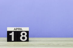 18 Dag 18 van april van maand, kalender op houten lijst en purpere achtergrond De lentetijd, lege ruimte voor tekst Royalty-vrije Stock Fotografie