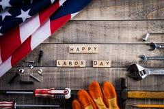 Dag van de Arbeid, de vlag van de V.S. Amerika met vele handige hulpmiddelen op houten textuur als achtergrond stock foto