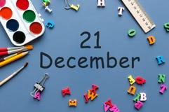 21 Dag 21 van december van december-maand Kalender op zakenman of schoolkindwerkplaatsachtergrond Bloem in de sneeuw Stock Foto