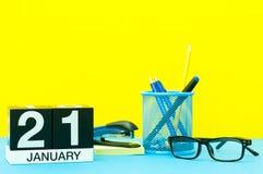 21 Dag 21 van januari van januari-maand, kalender op gele achtergrond met bureaulevering Bloem in de sneeuw Stock Afbeeldingen