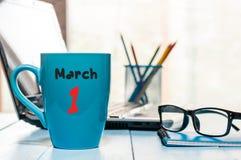 1 Dag 1 van maart van maand, kalender op de kop van de ochtendkoffie, bedrijfsbureauachtergrond, werkplaats met laptop en glazen Stock Foto