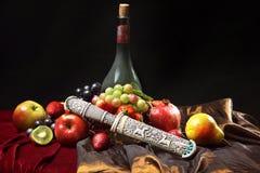 Daga vieja en la funda, todavía del holandés vida clásica con la botella polvorienta de vino y frutas en un fondo azul marino, ho Imagen de archivo libre de regalías
