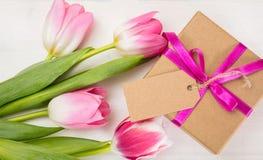 dagblomman ger mödrar mumsonen till Rosa tulpan och en gåva för tomt kort på vit bakgrund, bästa sikt, kopieringsutrymme Arkivfoton